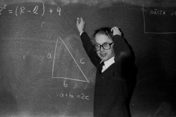 Teacher scratching his head in front of a blackboard